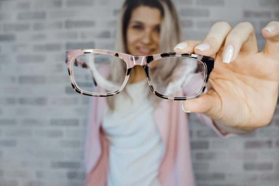 Image of woman holding eye glasses
