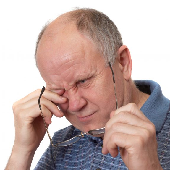 image of man rubbing eyes